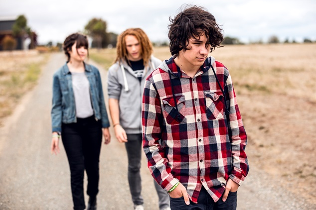 A young male teenager in a flannel shirt walking along a country road ahead of his two friends, who are speaking with each other.