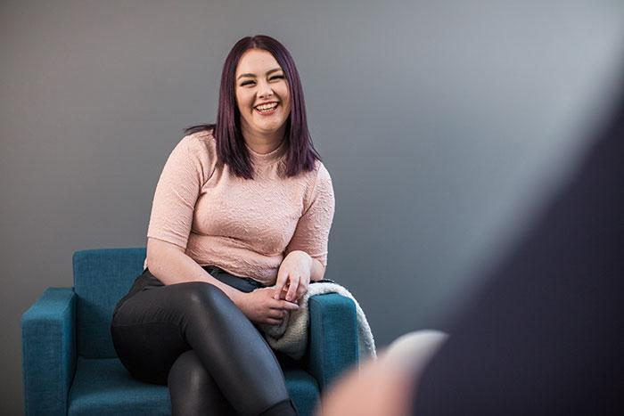 Young person in pastel top smiling on armchair