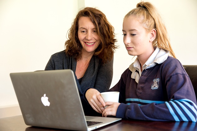Schoolchild and parent look at Macbook screen