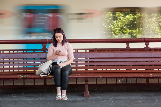 Young person sat on wooden bench, using mobile phone