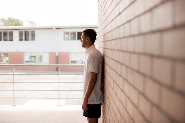 Side profile of person in Summer clothing leaning against brick wall of school exterior