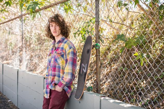 Young skateboarder leaning against a fence