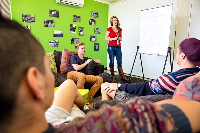 Group of students sat around as one person leads a class using a flip chart.
