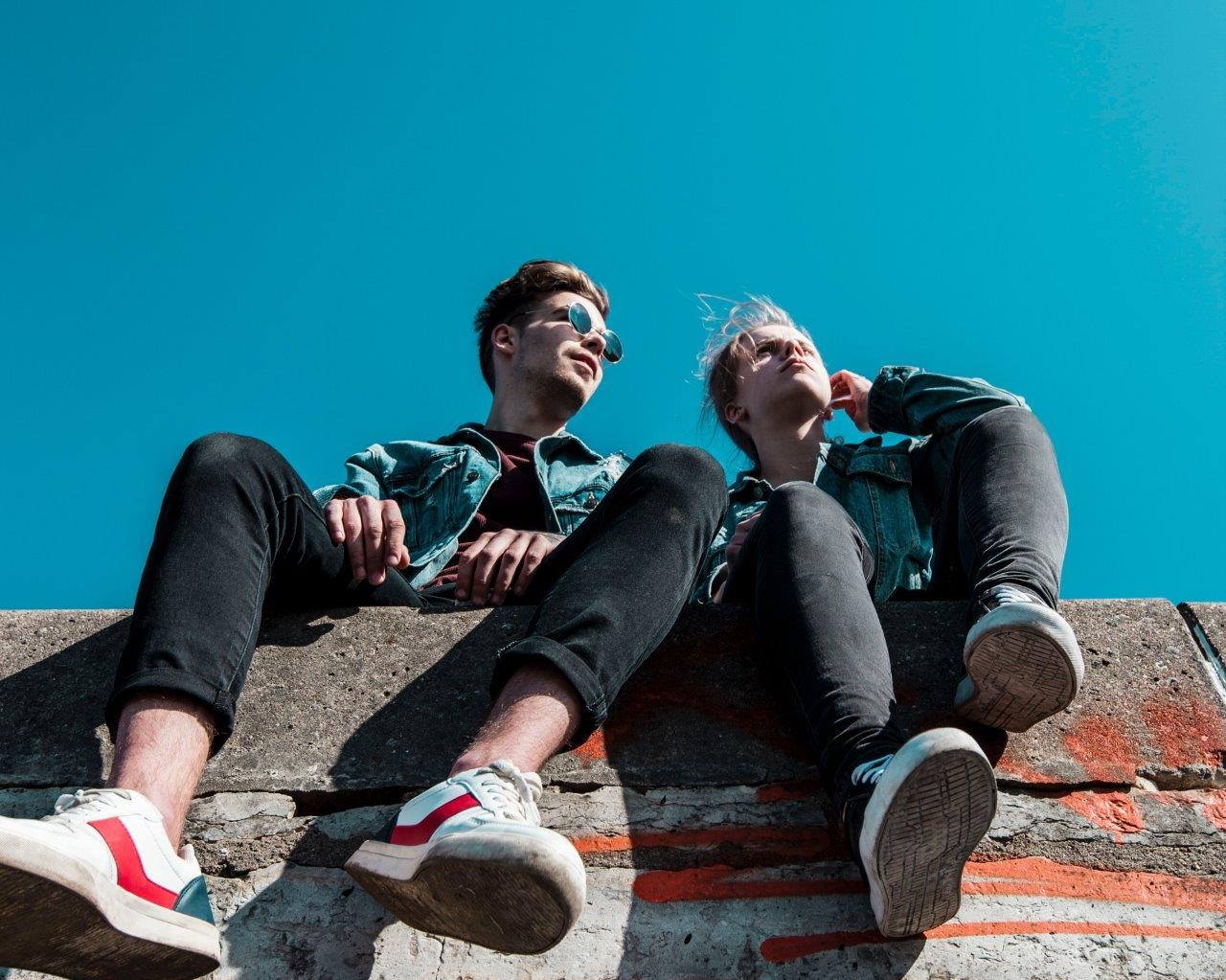 2 people sat on a wall with a blue sky behind them