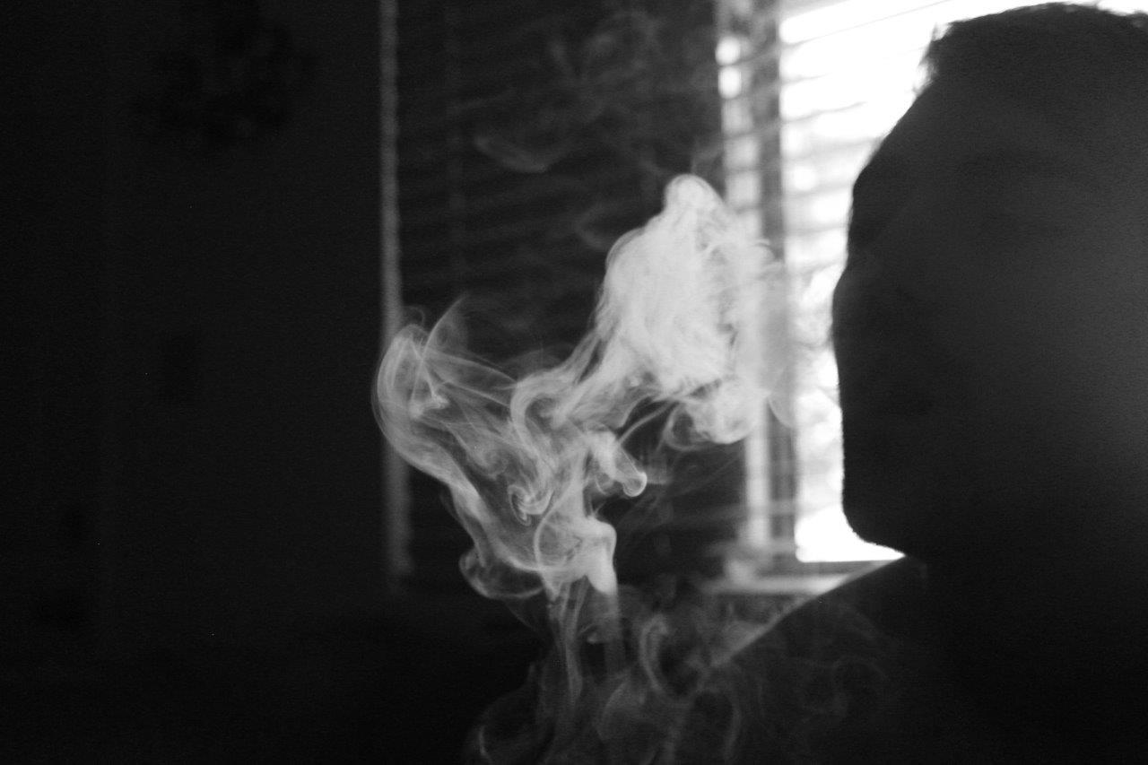 Almost silhouetted face blows smoke out in a dimly lit room, black and white.