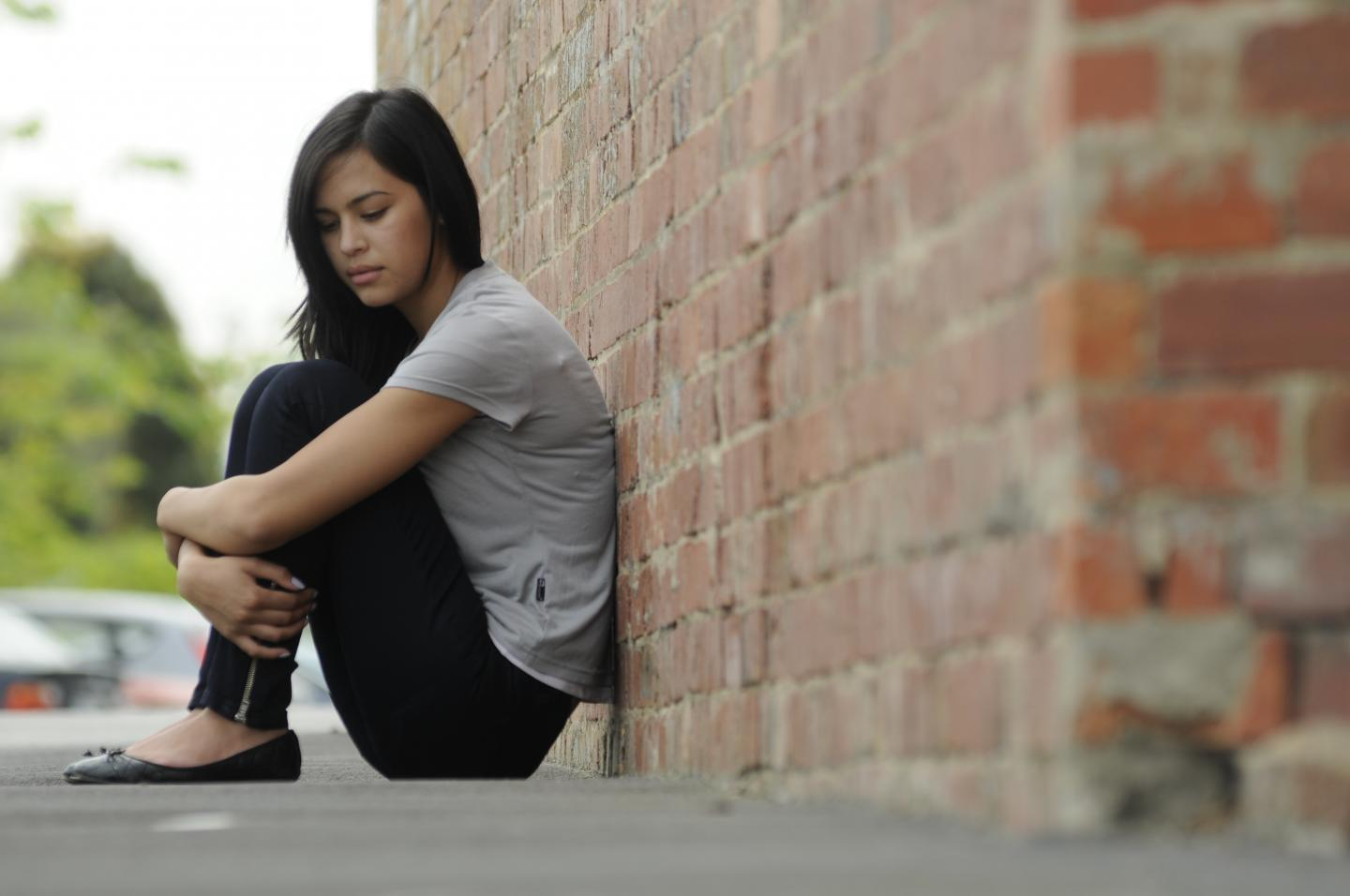 Young person sat curled against a brick wall