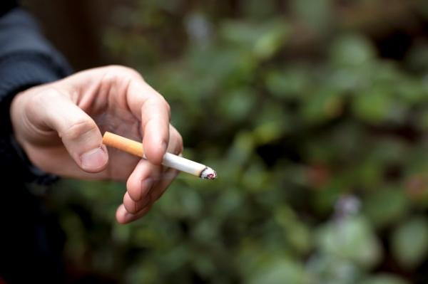 Shot of a single hand holding a lit, half-smoked cigarette between two fingers