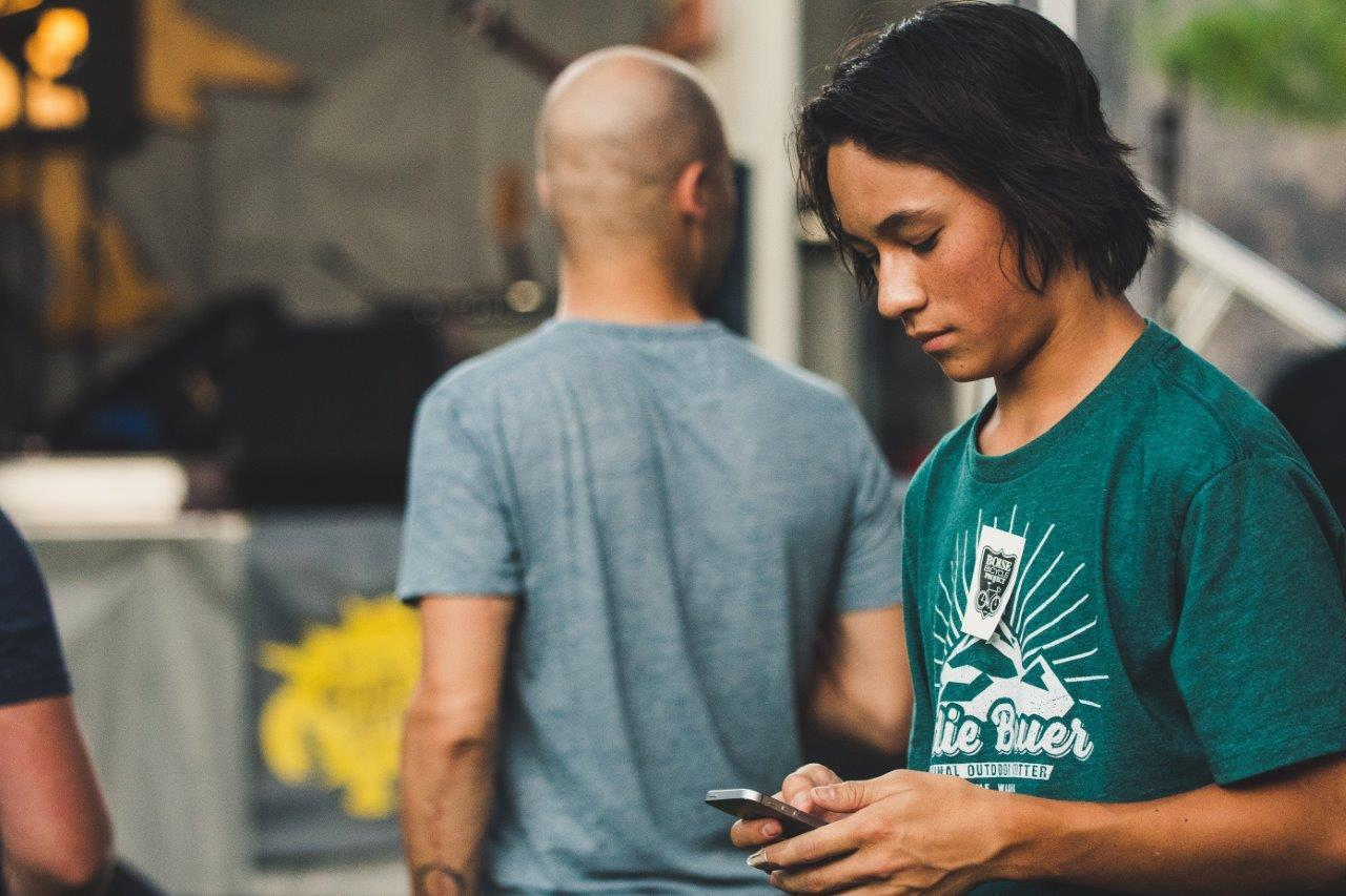 Young person in green top on cell phone in outdoor area