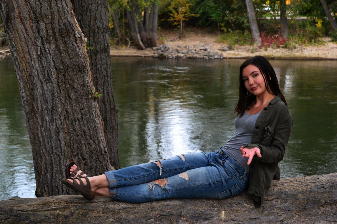 girl sits on tree by lake in jeans