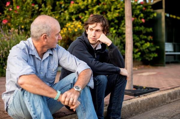 Young person sat with father on sidewalk curb.