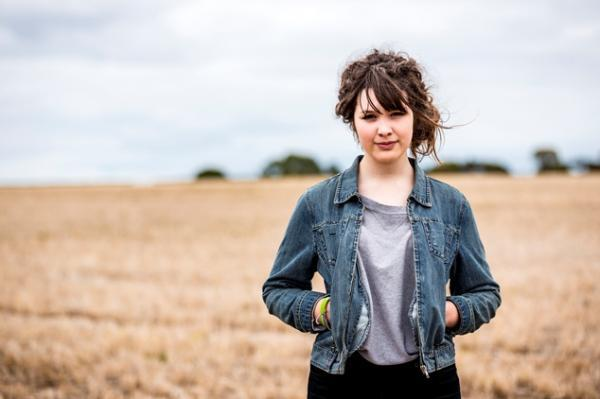 Young person in denim jacket stands in a wheat field.
