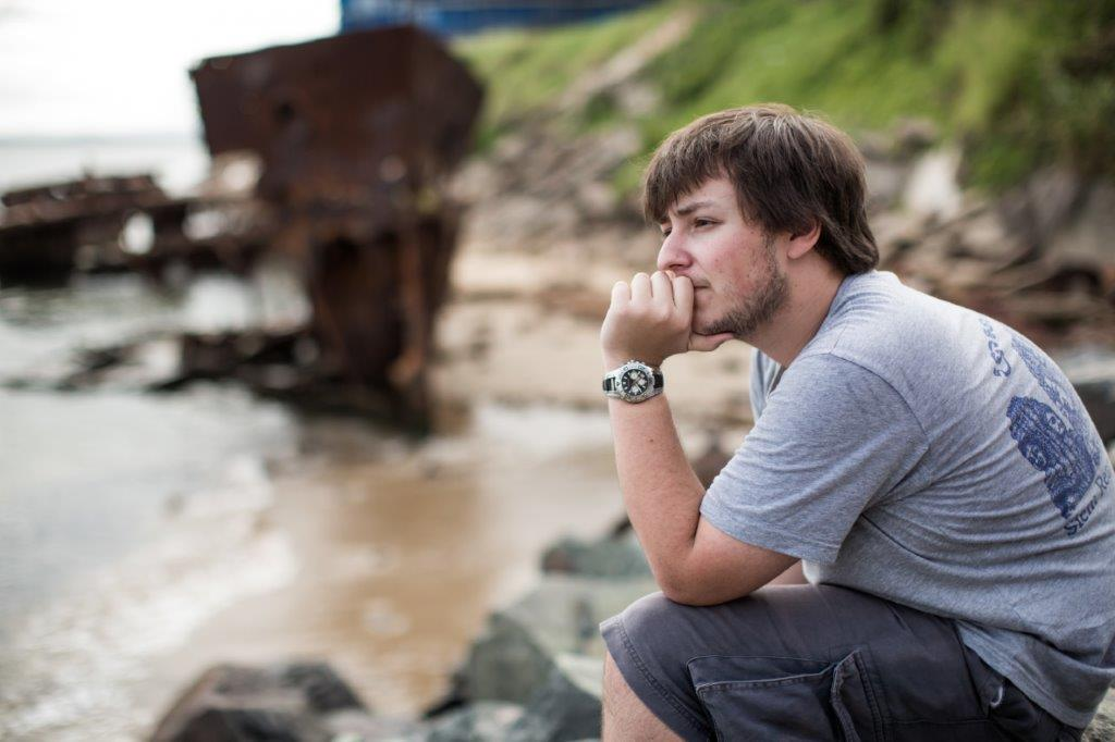 Young person stares contemplatively out at sea